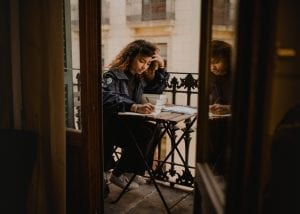 A curly-haired girl that is writing in a notebook with a two books in the table